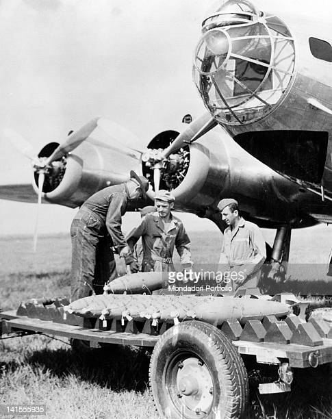 Some soldiers loading bombs on a trolley under the fuselage of an American bomber in Virginia United States August 1939