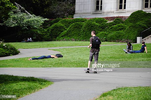 CONTENT] Some students walking around resting in the grass and skating in the university campus at University of California Berkeley San Francisco...