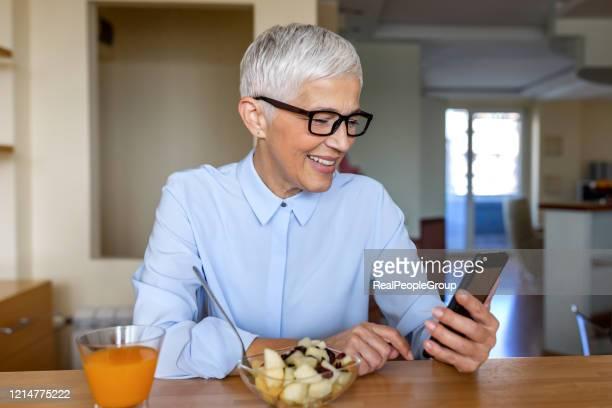 一部のテキストは、あなたの一日を明るくすることができます。ホームオフィスで働く美しい成熟した女性 - 女性建築家 ストックフォトと画像