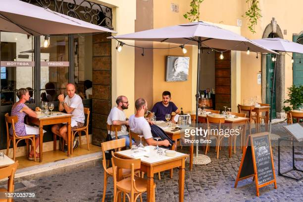 some tourist enjoy the italian cuisine in a lovely restaurant in the jewish ghetto of rome - image title stock pictures, royalty-free photos & images