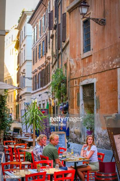 some tourists enjoy life and the italian cuisine in a lovely restaurant near piazza navona - image title stock pictures, royalty-free photos & images