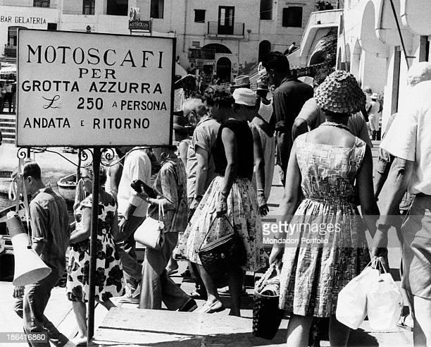 Some tourists flock at the pier to Grotta Azzurra , near an advertising handwritten billboard. Capri , Italy, 1962.