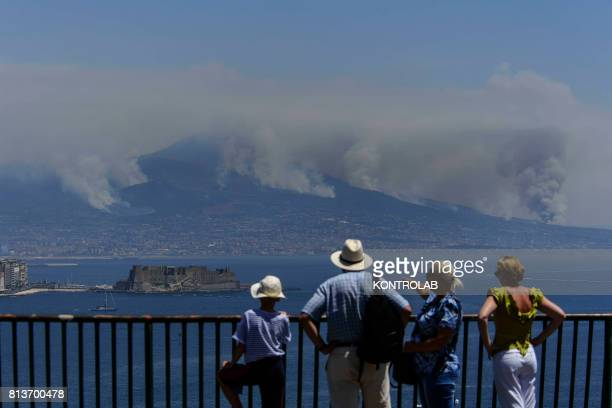 Some tourists look at Vesuvius with a vast fire on the slopes.