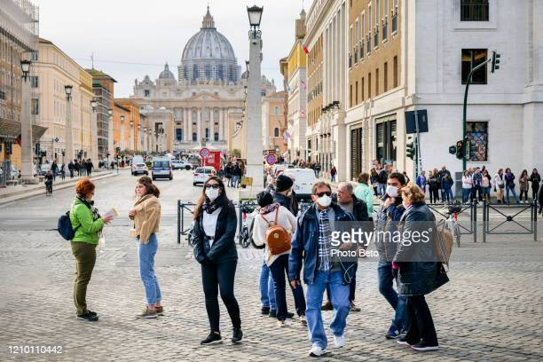 some tourists with medical masks near the square of st. peter's basilica in rome - italy stock pictures, royalty-free photos & images