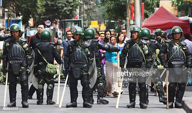 Some Uighur people walk near police as they form a line across a street on July 8 2009 in Urumqi the capital of Xinjiang Uighur autonomous region...