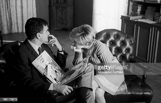 Some vinyl records resting on Italian singer Teddy Reno . Italian-born Swiss singer and actress Rita Pavone looking at him. 1968.