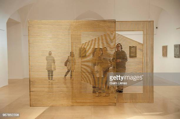 Some visitors look at a sculpture hanging from the ceiling during the press opening of the retrospective exhibition of Eusebio Sempere one of the...