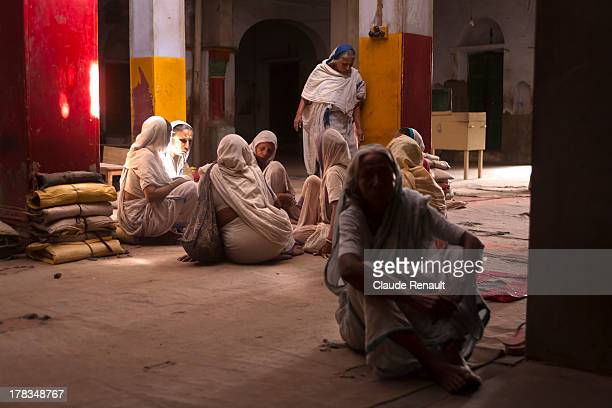 CONTENT] Some widows resting in one building of the Ashram before heading toward the big room where they will sing Bhajan Kirtan