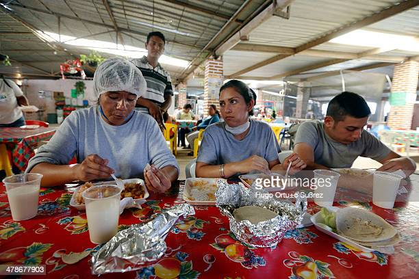 Some women eat food prepared for those affected by the spill of molasses in the dam El Hurtado. Over 500 tons of dead fish were removed from the dam,...