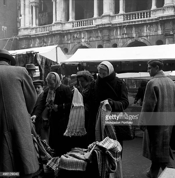 Some women shopping at an openair market stall selling scarfs Vicenza 1955