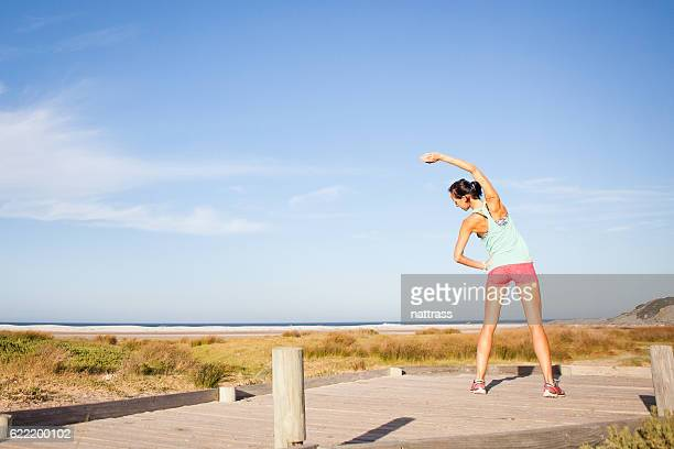 Some yoga stretches on the boardwalk by the beach