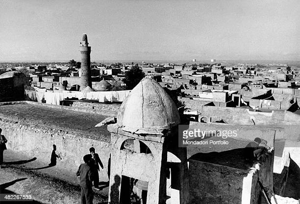 Some young Iraqi men standing beside a tower in ruins with a bell inside In the distance the old city and some oil reservoirs Kirkuk December 1956