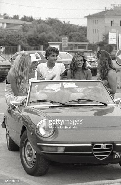 Some young people sitting on an Alfa Romeo Spider Forte dei Marmi August 1982