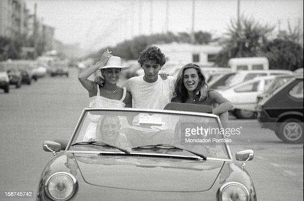 Some young people travelling on board an Alfa Romeo Spider Forte dei Marmi 1982