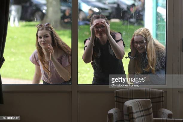 Some young women try to get a glimpse of Labour leader Jeremy Corbyn addressing a rally of supporters at Beeston Youth and Community Centre as he...