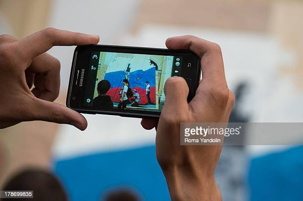Somebody takes a photo with Samsung smartphone of a big graffiti with a flag of Russia that was painted on a puzzle during National Flag Day in St....
