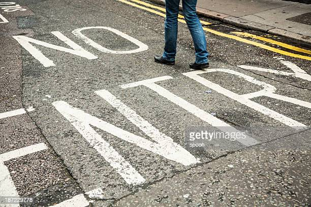 Someone crossing 'No Entry' sign, Breaking law.