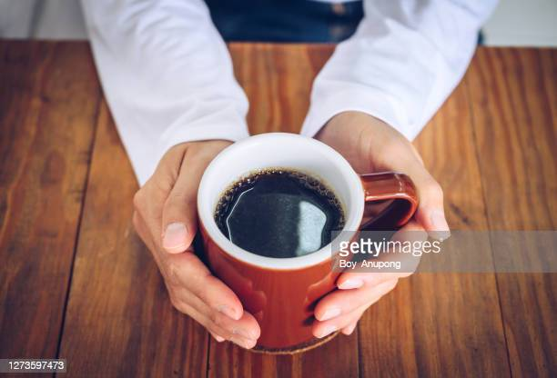 someone hands holding a mug of black coffee before drinking. - コーヒー ストックフォトと画像