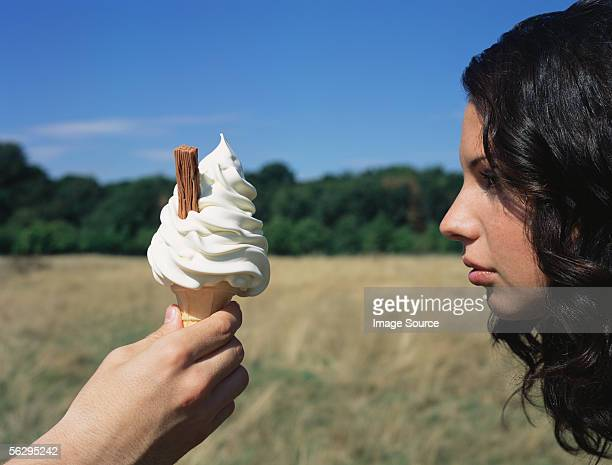 Someone holding an ice cream in front of a woman's face