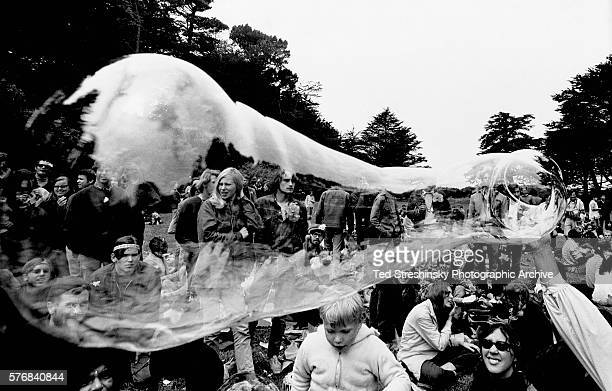 Someone in a crowd of hippies blows a giant bubble which refracts the view of the crowd during a lovein at San Francisco's Golden Gate Park