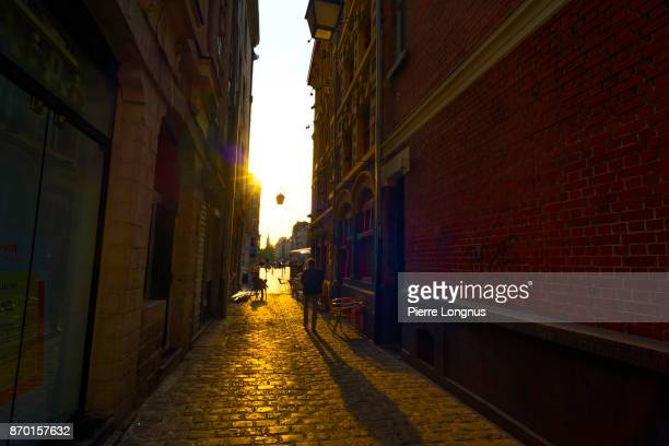 Someone in the street walking towards the sunset light coming in the Rue du Petit Paon, Lille, north of France