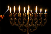 Someone lighting the last candle of a Menorah