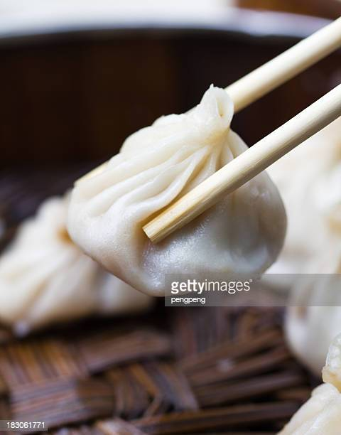Someone picking up a dumpling with chopsticks