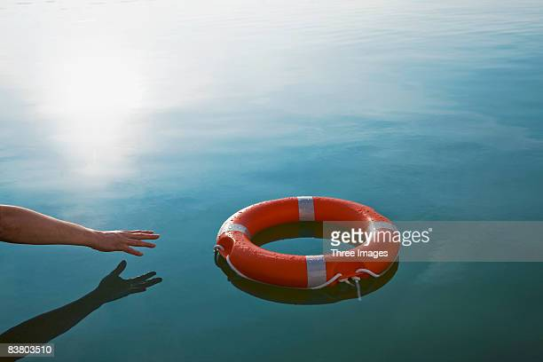 someone reaching out for a life-ring  - survival stock pictures, royalty-free photos & images