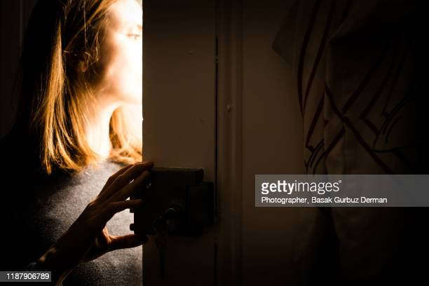 someone rings doorbell in the middle of the night and a woman opens the door - door stock pictures, royalty-free photos & images