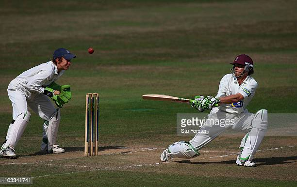 Somerset batsman James Hildreth hits a ball towards the boundary on his way to a century watched by Hampshire wicketkeeper Michael Bates during day...