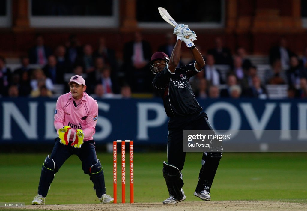 Somerset batsman Kieron Pollard hits six runs watched by Middlesex wicketkeeper Adam Gilchrist during the Friends Provident T20 match between Middlesex and Somerset at Lords on June 9, 2010 in London, England.