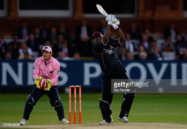 Somerset batsman Kieron Pollard hits six runs watched by Middlesex wicketkeeper Adam Gilchrist during the Friends Provident T20 match between...