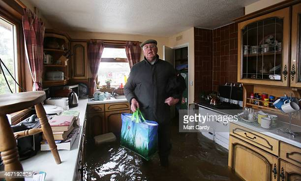 Somerset farmer, 66-year-old Bob Hall, stands in his flooded kitchen as he loads some of his processions onto a tractor trailer as he prepares to...