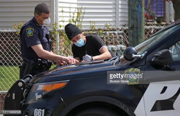 Somerville Police Officer issues a summons to a pedestrian by Highland Ave in Somerville, MA on April 29, 2020. Somerville will require face masks in...