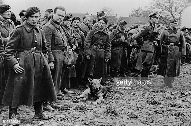 captured In Nazi's Latest 'Blitzkrieg' Two German soldiers at the right don't appear to be very much concerned over these prisoners shown in a camp...