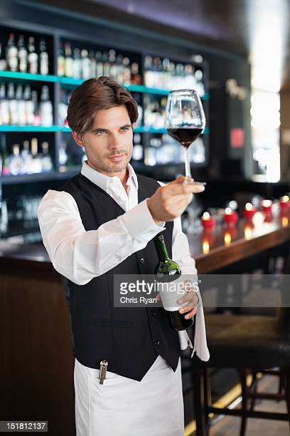 Sommelier examining glass of red wine in bar