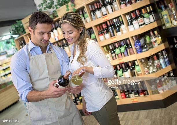 Sommelier helping woman buy a bottle of wine