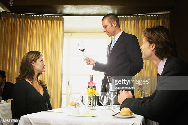 Sommelier holding glass of red wine