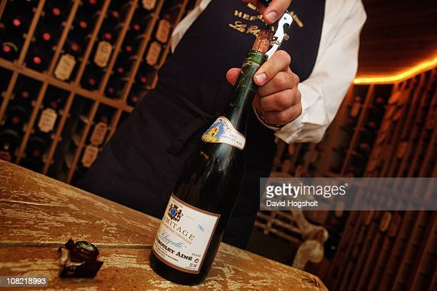 Sommelier JeanLuc Chapel uncorking a bottle of 1961 'La Chapelle' Rhone wine in order to put a new cork in it August 5 2009 in the cellar of a...