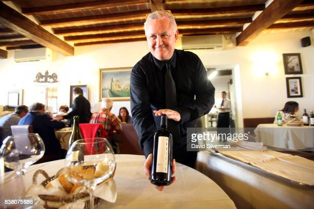 Sommelier Marco Pizzigoni serves red wine at Al Vèdel the Osteria restaurant of the Podere Cadassa a farm renowned for its cellaraged Culatello...