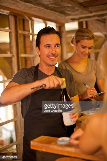 Sommelier opening bottle of wine in wine shop