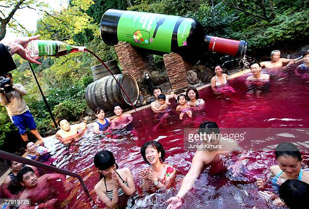 A sommelier pours a bottle of Beaujolais Nouveau into an open air wine spa at the Hakone Kowakien Yunessun on November 15 2007 in Hakone Kanagawa...