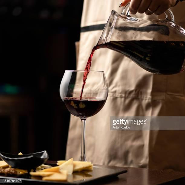 sommelier pours red wine from glass jug into wine glass on black background. close up shot. alcoholic drink or beverage - uvas cabernet sauvignon - fotografias e filmes do acervo