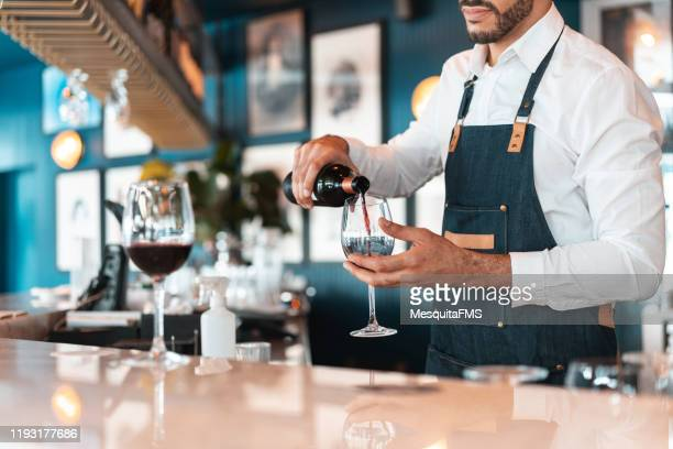 sommelier serving red wine in luxury hotel bar - maroon stock pictures, royalty-free photos & images