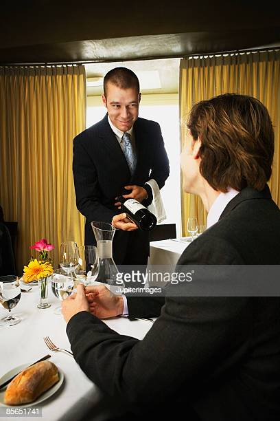 Sommelier showing wine to man