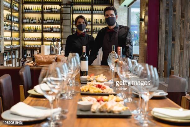 sommeliers die een winetasting gebeurtenis bij een kelder organiseren die gezichtsmaskers draagt - voedingsindustrie stockfoto's en -beelden