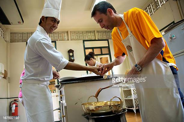 Sompop Nontaud cooking instructor at the Thai Cooking School at the Oriental Hotel looks on as American Scott DeGhetto prepares a curry