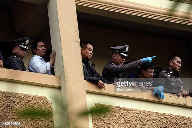 Somyot Poompanmoung, Lieutenant General of the Thai police, center, stands with other police officers on the balcony of an apartment block as a...