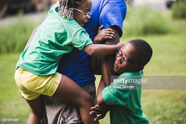 son and daughter play fighting father at parkland eco camp - naughty america stock pictures, royalty-free photos & images