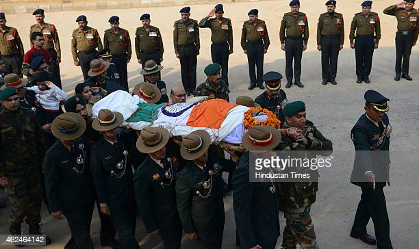 Son and daughter salute as colleagues and senior army officials carry the mortal remains of martyred hero Colonel Munindra Nath Rai during cremation...